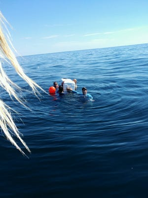 Four men hung onto a cooler for eight hours while waiting to be rescued 23 miles offshore after their boat sank Sunday morning.