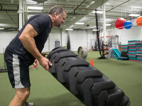 Kevin Kansman flips a large tire during his workout.
