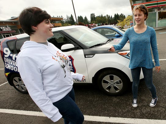 Catherine Hinson, 15, (right) hands Jhordan Mills,