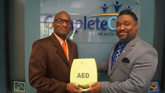 J. Curtis Edwards (right), president and chief executive officer, CompleteCare Health Network, presents Pastor James Dunkins of Shiloh Baptist Church with an automated external defibrillator.
