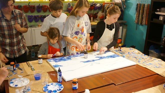 Jessi Davison, Melissa Piltin, Jack and Taylor Roberts, and Kimsey Fiddie work on last year's art project