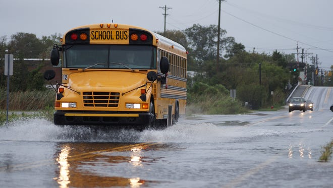 A school bus plows through a water-covered road in Lewes last month. Gov. Jack Markell is asking for $2.2 million in federal aid after two days of massive rain hit the state on Sept. 29 and 30.