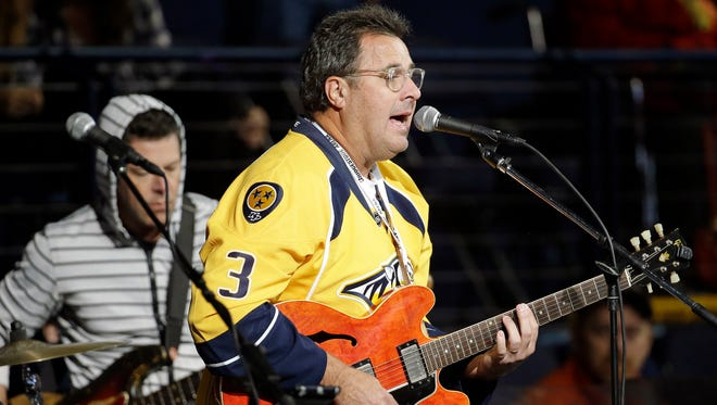 Country music star Vince Gill performs during an intermission at an NHL hockey game between the Nashville Predators and the Chicago Blackhawks on Oct. 23, 2014, in Nashville.