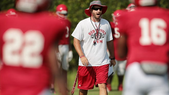 Germantown High School coach Chris Smith directs his team during their first practice of the season in full pads at their practice field behind thew school. Despite the hot day, Germantown ran plays and scrimmaged taking frequent water breaks.