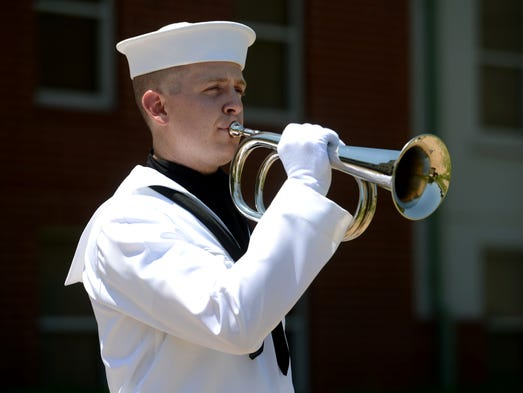 Airman Apprentice Bryson Held practices playing taps outside a barracks building aboard Naval Air Station Pensacola on Thursday while preparing to play for two Memorial Day performances this weekend.