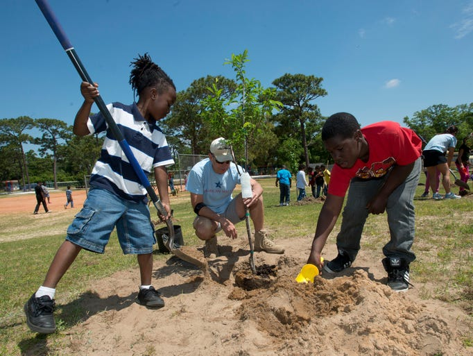 O.J. Semmes Elementary School students Willie B. Floyd, left, and Tydavious Lewis, right, help in planting a fruit tree on the school's campus while Earth Day from volunteer Tom Torchia, center, offers them a few tips Tuesday morning April 22, 2014.