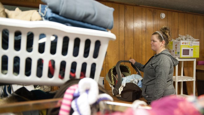 Brittany Borden picks up donated items at Stimens Apartment office Saturday night after being displaced from her apartment complex after a fire Wednesday.