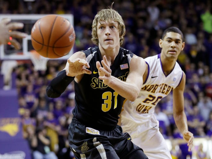 Wichita State guard Ron Baker, left, passes in front of Northern Iowa guard Jeremy Morgan during the first half of an NCAA college basketball game on Saturday, Feb. 8, 2014, in Cedar Falls, Iowa.
