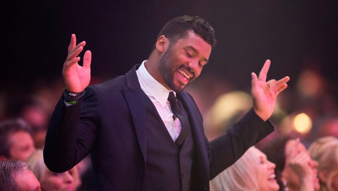 Seahawks quarterback Russell Wilson dances during a musical performance by actor Quinton Aaron during Celebrity Fight Night XXI at the JW Marriott Desert Ridge Resort & Spa in Phoenix on Saturday, March 28, 2015.