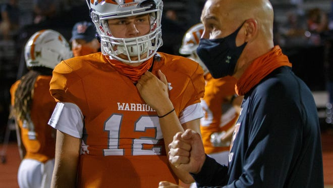 Westwood coach Anthony Wood, speaking with quarterback Matthew Lescano during last week's game against Lake Travis, and his Warriors were forced to postpone Friday's game against Hutto over COVID-19 concerns.