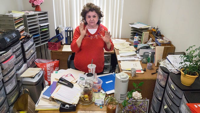 Carol Ann Donnelly laments the condition of her office, but it represents the many pieces of the Christian Service ministry she is responsible for at Church of the Holy Family in Novi.