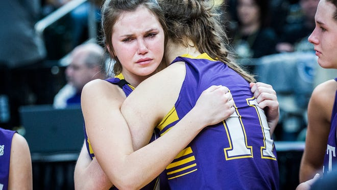 Caroline Herman (42) and Lauren Carie (11) console one another after Vincennes Rivet lost to Michigan City Marquette Catholic Saturday in the Class A girls' state championship game at Bankers Life Fieldhouse in Indianapolis.