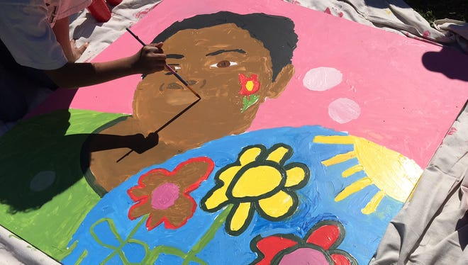 The children of the Cheatham Place public housing complex on Tuesday paint panels that will later be displayed on Jefferson Street.