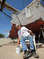 "Capt. Art ""Daddy Art"" Daniels takes a break while paiting his skipjack, City of Crisfield."