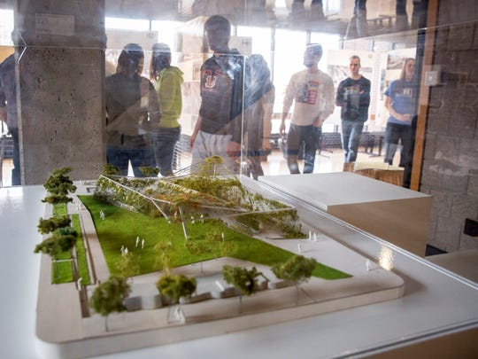 Fourth year architecture students on Feb. 15 at Ball State University look over an exhibit inside the College of Architecture and Planning. Ball State University's apprehension over Indiana University's plans to start an architecture program has been resolved through a partnership.