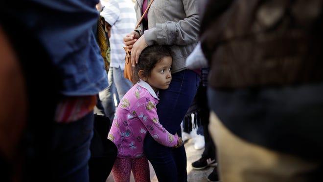 Nicole Hernández, una niña de Guerrero, abraza la pierna de su madre en Tijuana, México, quien espera junto a otras familias respuesta a su petición de asilo en EU.