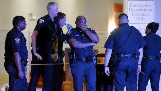 A Dallas police officer covers his face as he stands with others outside the emergency room at Baylor University Medical Center, July 8, 2016, in Dallas. Snipers opened fire on police officers in the heart of Dallas on Thursday night, killing five.