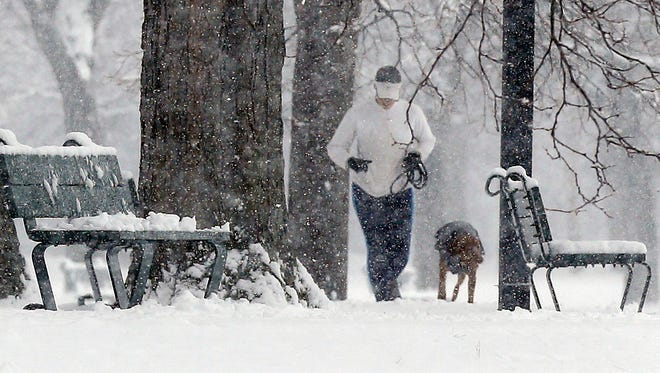 A woman jogs with a dog on the Esplanade in Boston, Saturday.