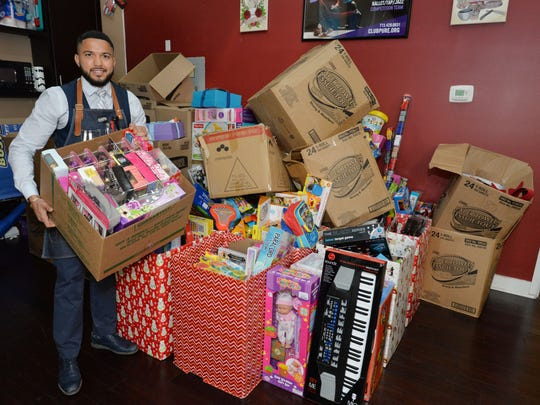 Jose Ruiz with some of the 1,000 toys that were collected during the 2nd Annual Toy Drive Block Party