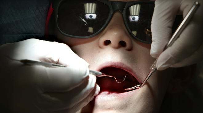 """Paxton Metz wears protective sunglasses to get his teeth cleaned and sealed on Oct. 8, 2012, at the Southern Illinois University School of Dental Medicine clinic in Alton, Ill., as part of """"Give Kids A Smile Day."""""""