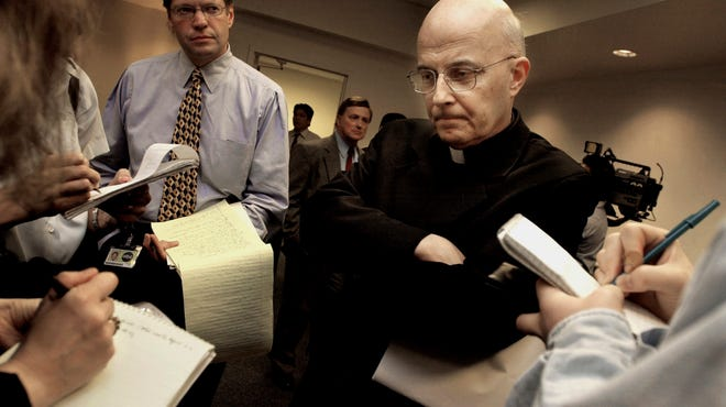 This April 17, 2002, photo shows Chicago Cardinal Francis George listening to reporters' questions  before he left for Rome to meet with Vatican officials and other American cardinals about the child sex abuse scandals in the United States.