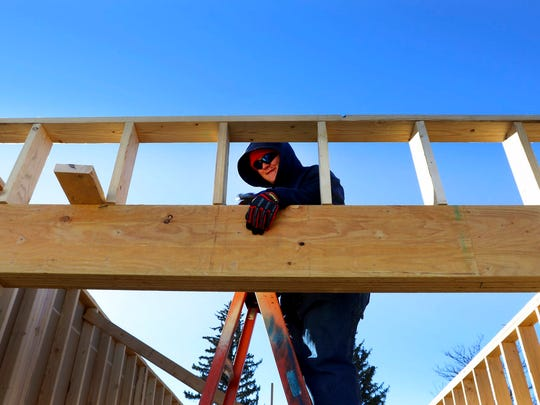 In a Wednesday, Jan. 17, 2018 photo, Mathew Wright, a junior, uses a hammer during a Habitat for Humanity build off 13th Street in Cheyenne. Students from the three Cheyenne comprehensive high schools are working on two twin homes, which will provide shelter for four families as opposed to one.