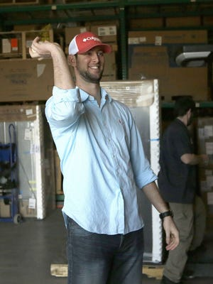 In this Thursday, Jan. 29, 2015, photo, New York Yankees pitcher Chris Martin playfully tosses a baseball at the Texas Appliance store warehouse where he used to work and play catch in Arlington, Texas. After suffering an injury while on the path to pitching Major League Baseball, Martin had shoulder surgery in 2007 and his throwing arm didn't respond so he figured his baseball career was over. After a while he started to work at Texas Appliance with his friend and in 2010, the pair started throwing a baseball in the appliance store warehouse during down time. Soon Martin realized his shoulder felt good and he began his return to pitching. (AP Photo/LM Otero)