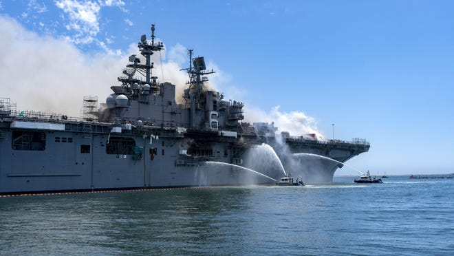 In a photo provided by the U.S. Navy, Port of San Diego Harbor Police boats fight a fire aboard the USS Bonhomme Richard at Naval Base San Diego on Sunday. Twenty-one people suffered minor injuries in an explosion and fire on the ship, military officials said.