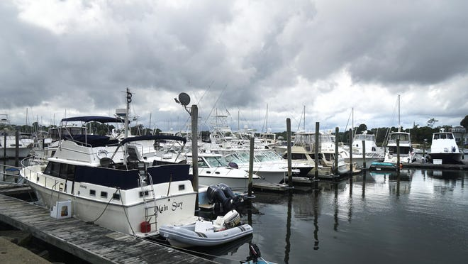Boats sit in the tranquil waters of Wickford Harbor Sunday afternoon, ahead of this week's expected storm.