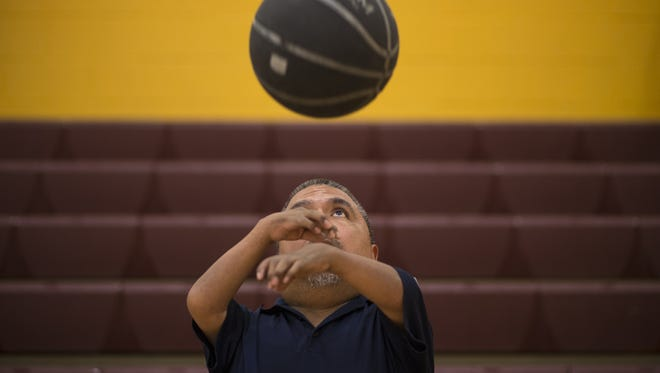 David Solano catches a basketball before the start of practice at Raul H. Castro Middle School in Phoenix.