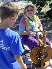 Weaver Annabell Younger of Stagecoach talks to a student as she spins wool from sheep she raised.