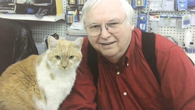 "Seiko the cat and Robert ""Bob"" Thomas of Hobby Haus. Seiko went missing Monday."