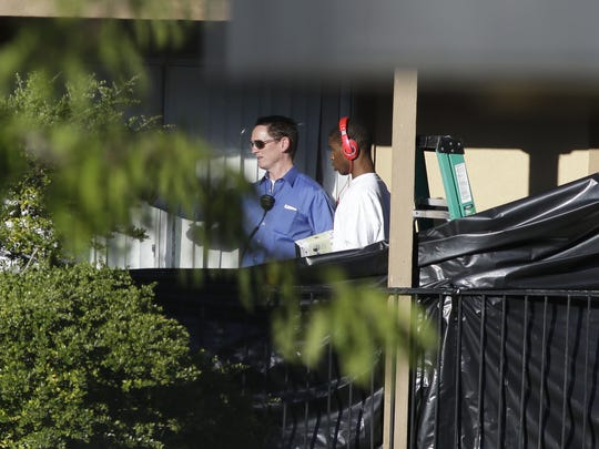 ADDS ID OF OFFICIAL - Dallas County Judge Clay Jenkins, left, leads a young man from an apartment in Dallas, Friday, Oct. 3, 2014, where Thomas Eric Duncan, the Ebola patient who traveled from Liberia to Dallas stayed last week. The family living there has been confined under armed guard while being monitored by health officials.