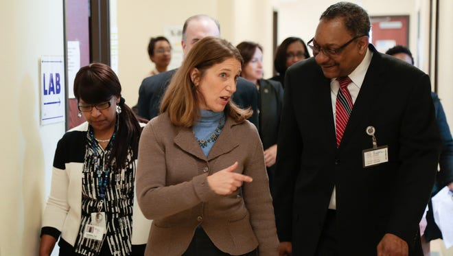 U.S. Department of Health and Human Services Secretary Sylvia M. Burwell talks with Hamilton Community Health Network Chief Executive Officer Clarence Pierce, M.S. while touring his facility in Flint on Thursday February 18, 2016 to view the federal response and recovery effort that her department is leading.
