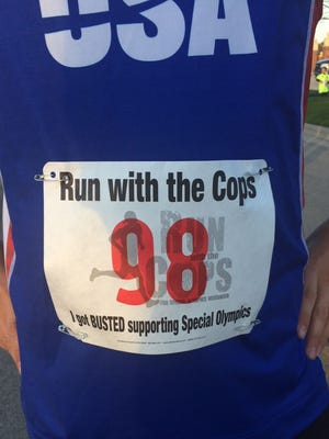Alex Guild of Lawrence wears a race bib on the front of his running top for the inaugural Run with the Cops to support local Special Olympics Wisconsin athletes outside St. Norbert College's Donald J. Schneider Stadium in De Pere on Thursday night, May 5, 2016. Guild, a two-time gold medalist in the Special Olympics World Games last year, was the top finisher in the Run with the Cops 5K Run/Walk.