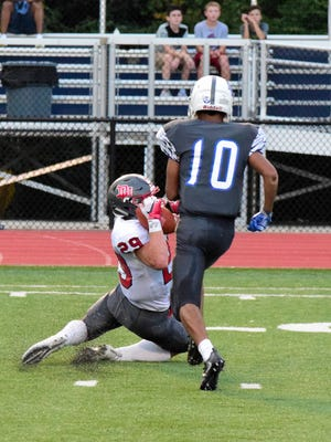 Cameron Barrett (29) of Dixie Heights pulls in a reception over the shoulder for a Colonels first down as Scott's Sabeon Turner (10) follows to complete the stop, August 26, 2016 -- Geoff Blankenship for the Enquirer