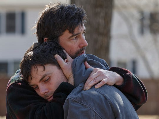 Joe (Kyle Chandler, rear) comforts Lee (Casey Affleck)