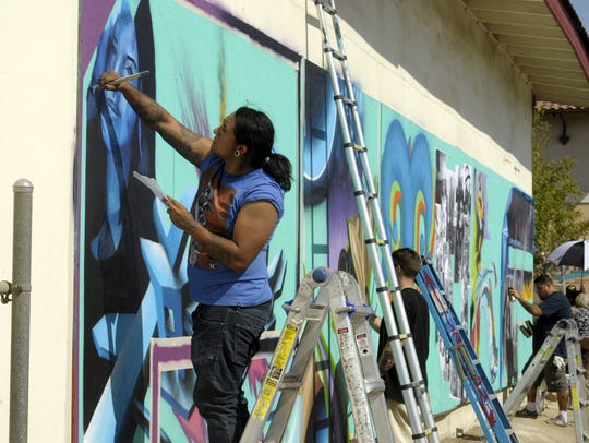 Ulices Gonzalez, left, of Texas, paints during the