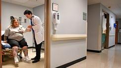 Dr Kevin Hogan wraps the arm of patient Deneen Barnes