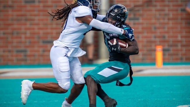 Georgia Southern outside linebacker Zyon McGee (21) tackles Coastal Carolina running back C.J. Marable (1) on Saturday at Brooks Stadium in Conway, S.C. Coastal Carolina won 28-14.