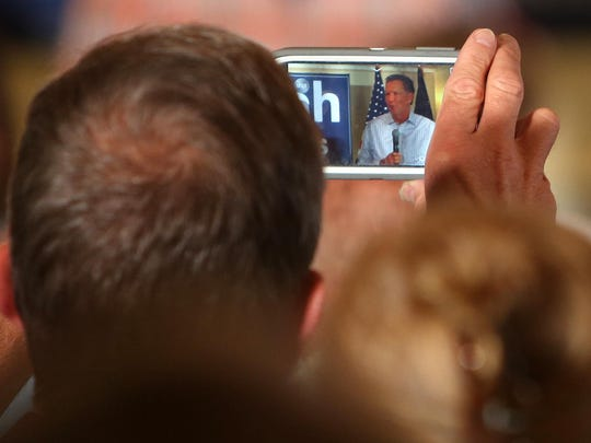 An audience members takes a photo as Gov. John Kasich speaks to a crowd at a town hall-style meeting Wednesday at the Portsmouth Country Club in New Hampshire.