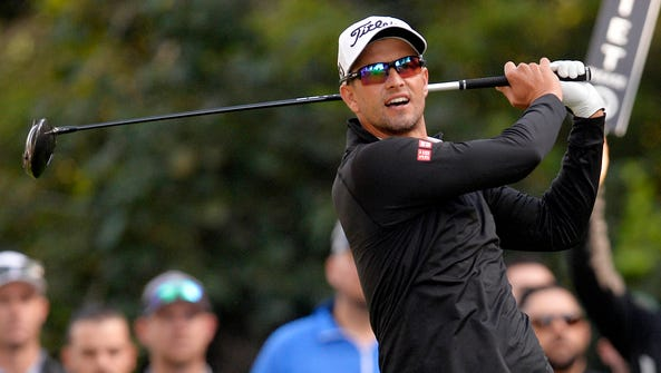 Adam Scott hits from the twelfth hole tee box during
