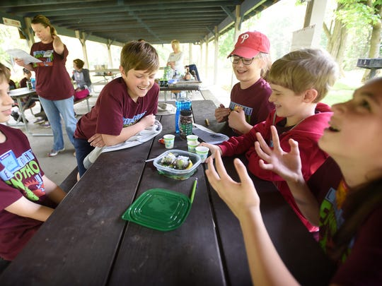 Forge Elementary School fifth grade students, from left, Luke Wolfe, Jack Wolfe, Maggie Webb, Luke Boyer, and Maddie Henry study the effects of pollution on wildlife Thursday, May 12, 2016, at Lebanon County's 23rd annual Elementary School Envirothon, held at Coleman Memorial Park in Lebanon.  The team is from the Palmyra Area School District. The envirothon is sponsored by the Lebanon County Conservation District.