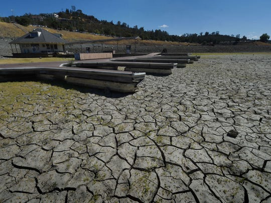Boat docks sit empty on dry land, as Folsom Lake reservoir
