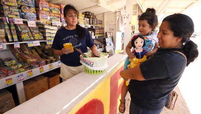 Isabel Mancillas and daughter Luz Mancillas, 3, purchase a few fireworks at the TNT Fireworks stand near the 14000 block of East Montana in this  June 2016 photo. Helping her at left is salesperson Veronica Alvarez. Fireworks sales in unincorporated areas of El Paso County could be banned this year if drought conditions worsen.