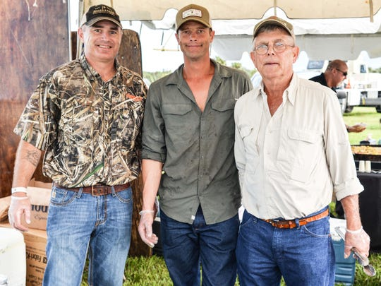 Wesley Purnell, left, takes a quick break from slicing delicious Adams Ranch brisket with John and Lee Adams