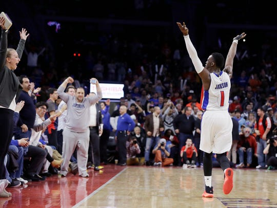 Reggie Jackson raises his arms to the crowd during the closing seconds of the Pistons' win Tuesday night.