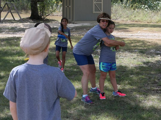 Amanda Krejci, former Sterling City elementary P.E. teacher and founder of the Sterling City Outdoor Education Program, helps campers properly through a Frisbee Tuesday, September 5, 2017.