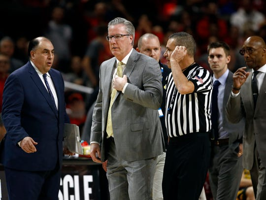 Iowa head coach Fran McCaffery, second from left, walks