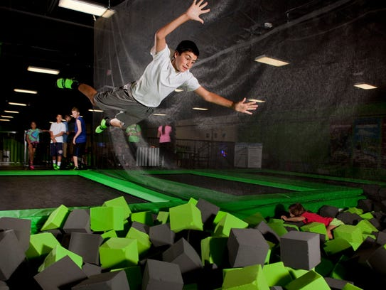 A young man jumps into a foam pit at a Launch Trampoline